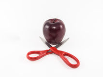 Scissors and red apple. Scissors look like to divide red apple isolated Stock Images