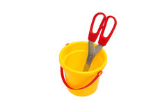 Scissors in a plastic bucket child. Scissors with red handle in the children yellow plastic bucket Royalty Free Stock Photos