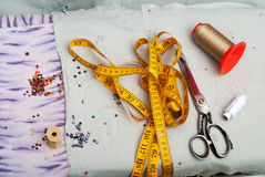 Scissors reel of thread, measuring tapes and natural fabric. Royalty Free Stock Photo
