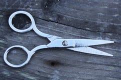 Scissors. School scissors on wood plank royalty free stock images