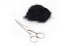 Scissors and scraps of black hair. Stock Image