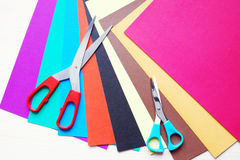 Scissors on sheets of multicolored paper Royalty Free Stock Image