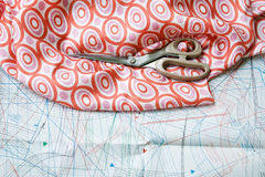 Scissors and silk material with pattern in background. Royalty Free Stock Photo