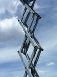 Scissors in the Sky. Hydraulic scissor lift extending upward Stock Image