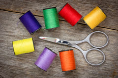 Scissors and spools of colored thread Royalty Free Stock Photo