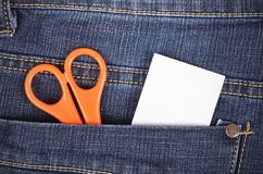 Scissors and sticker in the blue jeans pocket Stock Image