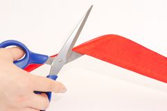 Scissors and tape. Scissors cutting a red tape Royalty Free Stock Image