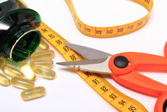 Scissors with tape measure and medical pills on white Stock Photography