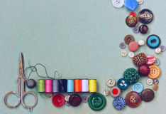 Scissors, thread, needle, thimble, various buttons Royalty Free Stock Photos