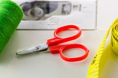 Scissors, thread , ribbon, sewing machine closeup. The process of working seamstresses royalty free stock photos
