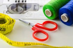 Scissors, thread , the tape on the sewing machine closeup. The process of working seamstresses stock image