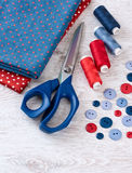 Scissors, threads, fabric and buttons on wooden table Stock Images