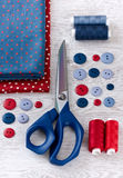 Scissors, threads, fabric and buttons on wooden table Stock Image