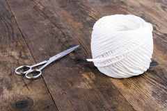 Scissors and twine ball, on a board. Royalty Free Stock Photos