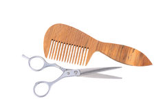 Scissors and a wooden comb Stock Photos