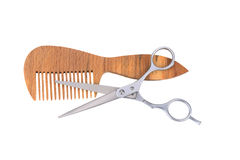 Scissors and a wooden comb Stock Photo