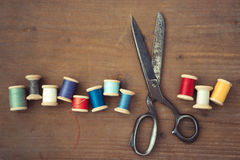 Scissors and wooden spools of thread Stock Photography