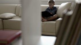 Scivolamento del metraggio della macchina fotografica: il ragazzo si siede su un sofà e legge un libro archivi video