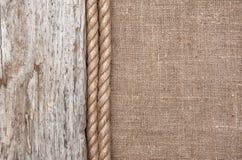 Säckvävbakgrund gränsade vid repet och gammalt trä Fotografering för Bildbyråer