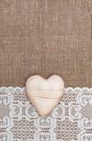Säckvävbakgrund med den spets- torkduken och trähjärta Royaltyfri Bild