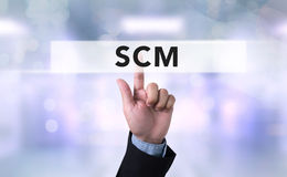 SCM Supply Chain Management concept. Business man with hand pressing a button on blurred abstract background Stock Image
