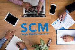 SCM Supply Chain Management concept. Business team hands at work with financial reports and a laptop, top view Royalty Free Stock Image