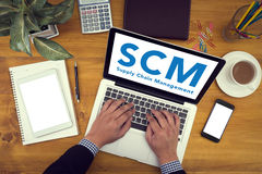 SCM Supply Chain Management concept. Corporate identity mock up on an hardwood desk with laptop, tablet, smartphone and a cup of coffee, man working Stock Images