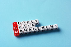 SCM Supply Chain Management. Written on dices on blue background Royalty Free Stock Images
