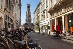 Scène de rue avec des vélos dans Bruge central, avec la 13ème tour de beffroi Image stock