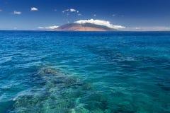 Scogliera in chiara acqua con la vista delle montagne ad ovest di Maui dalla riva del sud Sono riempiti sempre di veicoli dell'os Fotografie Stock Libere da Diritti