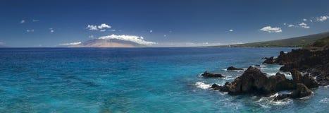Scogliera in chiara acqua con la vista delle montagne ad ovest di Maui dalla riva del sud Sono riempiti sempre di veicoli dell'os Immagini Stock Libere da Diritti