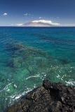 Scogliera in chiara acqua con la vista delle montagne ad ovest di Maui dalla riva del sud Sono riempiti sempre di veicoli dell'os Fotografia Stock Libera da Diritti