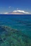 Scogliera in chiara acqua con la vista delle montagne ad ovest di Maui dalla riva del sud Sono riempiti sempre di veicoli dell'os Fotografia Stock