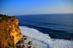 Scogliera con l'onda nell'ambito del tramonto Immagine Stock