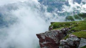 Scogliera con la bandiera dello svizzero nelle alpi su una mattina nebbiosa Immagini Stock Libere da Diritti
