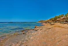 Scogliera del mare con gli ombrelli, il mare blu ed il cielo Immagini Stock