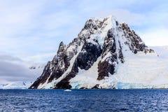 Scogliera di pietra ripida gigantesca coperta di neve e di mare in foregrou Fotografia Stock Libera da Diritti