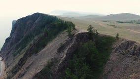Scogliera enorme della montagna della pietra della sabbia con i pini verdi nel lago Baikal Siberia Russia che stupisce vista aere video d archivio