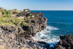 Scogliera nera ripida a Catania, costituita dai flussi di lava antichi dal vulcano Etna Fotografie Stock Libere da Diritti