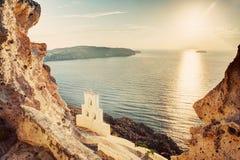 Scogliera, rocce vulcaniche e una cappella tradizionale sull'isola di Santorini, Grecia Fotografia Stock