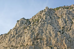 Scogliera rocciosa irregolare della pietra leggera contro cielo blu Fotografia Stock