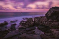 Scogliera sulla riva dell'oceano nel tramonto immagine stock