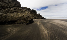 Scogliera sulla spiaggia con la sabbia nera in Karekare Immagine Stock