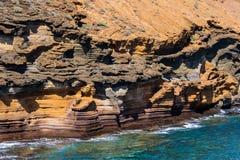 Scogliere arancio spettacolari e l'oceano - immagine fotografie stock
