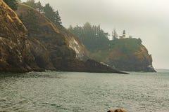 scogliere del mare con i pini e una casa leggera immagini stock libere da diritti