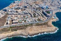 Scogliere della spiaggia, case colourful e vie della città di Qawra a St Paul ' area della baia di s nella regione settentri fotografia stock libera da diritti