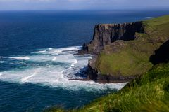 Scogliere di Moher all'oceano di Alantic in Irlanda occidentale con le onde che battono contro le rocce immagine stock libera da diritti