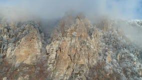 Scogliere enormi e vecchie su un fianco di una montagna coperto dagli arbusti e conifere congelate in nuvole grige contro cielo b video d archivio