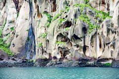 Scogliere tipiche del basalto con le caverne per gli uccelli marini sopra il mare del turchese su Heimaey, Islanda immagini stock libere da diritti