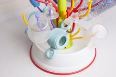 Scolapiatti in pieno degli oggetti di plastica delle stoviglie del bambino Immagine Stock